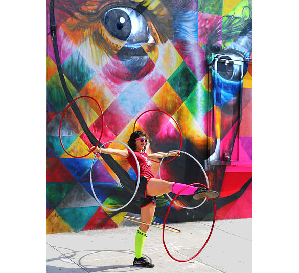"Street performer in front of a ""Kobra"" mural"