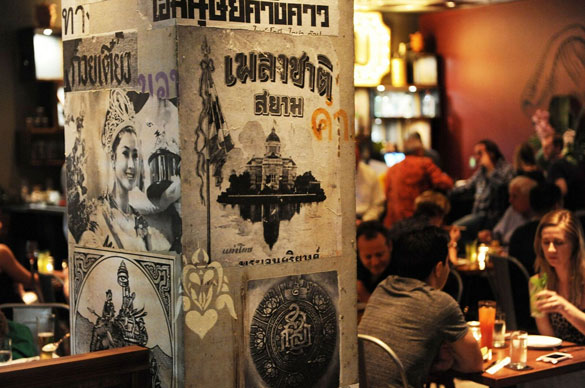 NaiYaRa Restaurant boasts an ecclectic mix of vintage Thai posters, reclaimed wood tables and rich red banquettes