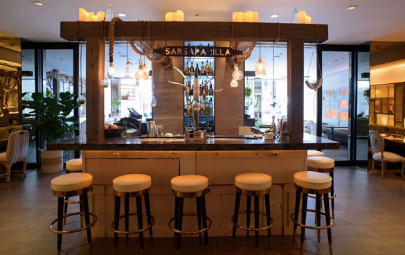The Sarsaparilla Club bar is decorated with custom metal accents, draped rope lanyards and blown glass pendant lighting.