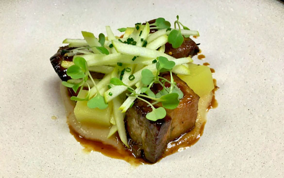 Chef Balloo's signature Roast Pork lechon topped with microgreens and tart granny smith apples