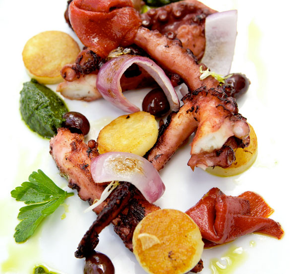 Grilled octopus is served with roast red peppers, kalamata olives, golden potatoes and salsa verde