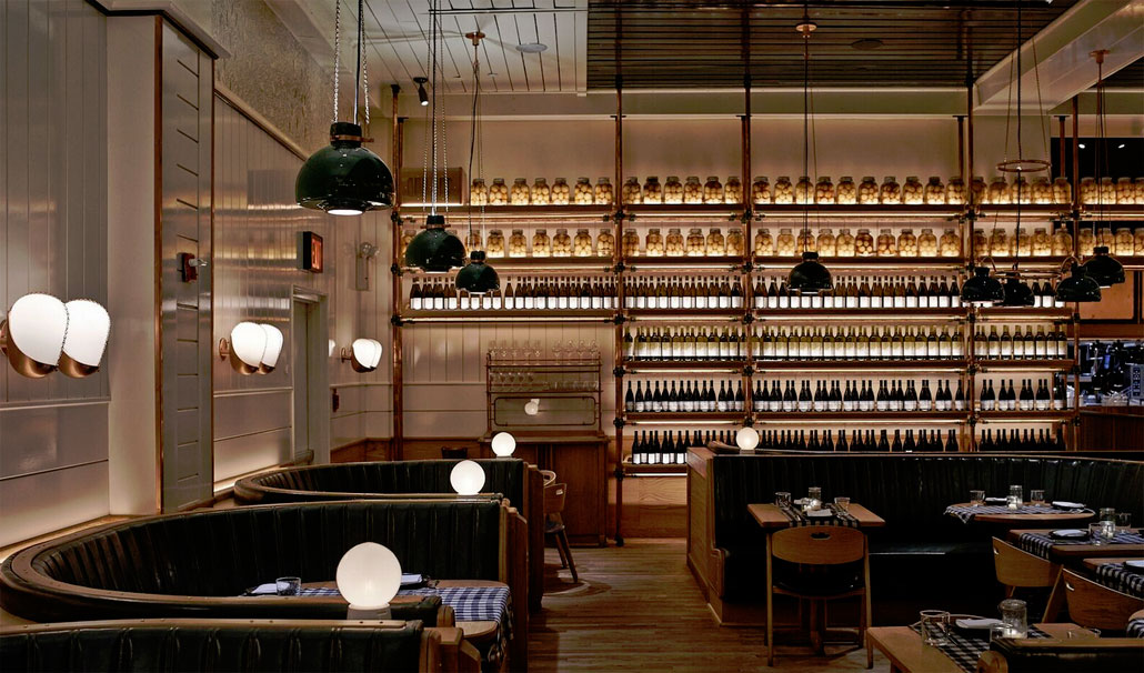 Awash in the glow of backlit bottles of wine and preserved citrus, Upland's dining room dazzles